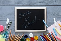 Kids supplies on on grey wooden desk, back to school background written on chalkboard for modern primary education, new year start. Color pencils, multicolored stock photography