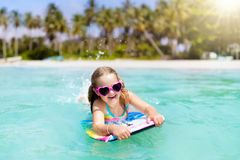 Kids surf on tropical beach. Vacation with child. Royalty Free Stock Photography