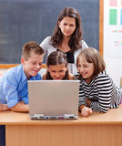 Kids surfing the internet. Kids surfing on the internet, watching unsafe content. Teacher stands behind and worries about Royalty Free Stock Images