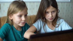 Kids surfing internet together on laptop. Girl friends sitting in front of monitor and pushing keyboard buttons. home education, online surfing and school stock video