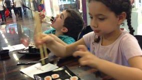 Kids in sushi restaraunt stock video footage