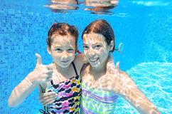 Kids swim in pool underwater Stock Photo
