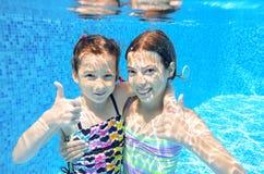 Kids swim in pool underwater