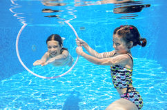 Kids swim in pool underwater Royalty Free Stock Images
