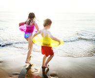 Kids with swim rings playing at the beach stock photo