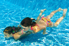 Kids swim underwater in pool Stock Photos