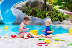 Kids at a swiming pool. Happy baby boy and little curly toddler girl, brother and sister, playing with toy buckets and plastic shovel next to a swimming pool in Stock Image