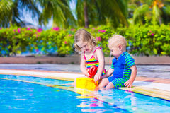 Kids at a swiming pool. Happy baby boy and little curly toddler girl, brother and sister, playing with toy buckets and plastic shovel next to a swimming pool in Royalty Free Stock Photos