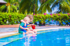 Kids at a swiming pool. Happy baby boy and little curly toddler girl, brother and sister, playing with toy buckets and plastic shovel next to a swimming pool in Stock Photos