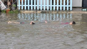 Kids are swimming in a flooded street of Pathum Thani in October 2011.  Royalty Free Stock Photos