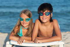 Kids with swimming goggles on the beach Stock Image