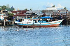 Kids swimming in harbor. Kids swimming in sea in harbor near by wooden boat in Sorong (Papua Barat, Indonesia stock photos