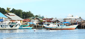 Kids swimming in harbor. Kids swimming in sea in harbor near by wooden boats in Sorong (Papua Barat, Indonesia Stock Photos