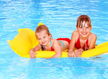 Kids swimming on inflatable beach mattress. Royalty Free Stock Photos