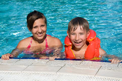 Kids in a swimming pool. Smiling cute kids in a swimming pool in sunny day Stock Image