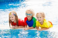 Kids in swimming pool. Children swim. Family fun. Kids play in swimming pool. Children learn to swim in outdoor pool of tropical resort during family summer royalty free stock photography