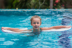 Kids in swimming pool. Children swim outdoors. Toddler child during vacation in a tropical resort with palm trees. Stock Image