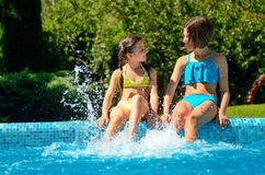 Kids in swimming pool have fun and splash in water Royalty Free Stock Photos
