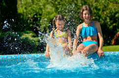 Kids in swimming pool have fun and splash in water Royalty Free Stock Photo