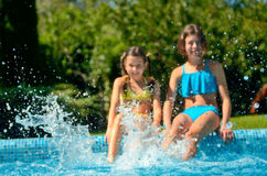 Kids in swimming pool have fun and splash in water Royalty Free Stock Images