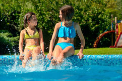 Kids in swimming pool have fun and splash in water Royalty Free Stock Image