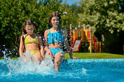 Kids in swimming pool have fun and splash in water Stock Photos