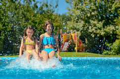 Kids in swimming pool have fun and splash in water Stock Image