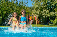 Kids in swimming pool have fun and splash in water Stock Photography
