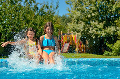 Kids in swimming pool have fun and splash in water Stock Images