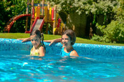 Kids in swimming pool have fun in water, children on family vacation Royalty Free Stock Photos