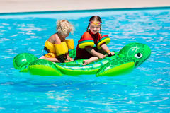 Kids in swimming pool with inflatable toy Stock Image