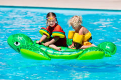 Kids in swimming pool with inflatable toy Stock Photo