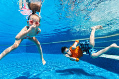 Kids  swimming underwater. Kids having fun playing underwater in swimming pool on summer vacation Royalty Free Stock Photo