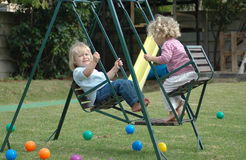 Kids on swing. Two blond caucasian white girls on a swing having great fun in the garden at home Stock Photos