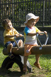 Kids on swing in the park. A blond caucasian white girl and a boy on a swing having great fun in the park Stock Photos