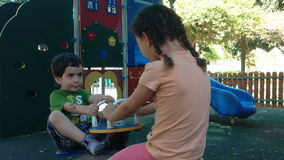 Kids swing together on playground stock footage