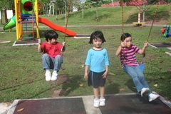 Kids swinging. Happy girls and boy swinging in the park Stock Photos