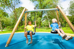 Kids on swings staring at each other and sit. On them on the playground Stock Photo