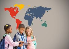 Kids on tablet in front of colorful world map Royalty Free Stock Photography
