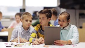 Kids with tablet pc programming at robotics school stock video