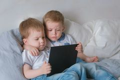 Kids with tablet. Two boys twins toddlers looking cartoon at tablet lying on the bed. Kids with tablet. Two boys twins toddlers looking cartoon at tablet lying stock photography