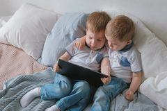 Kids with tablet. Two boys twins toddlers looking cartoon at tablet lying on the bed. royalty free stock photos