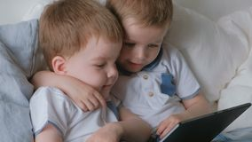 Kids with tablet. Two boys twins toddlers looking cartoon at tablet lying on the bed. Kids with tablet. Two boys twins toddlers looking cartoon at tablet lying stock footage