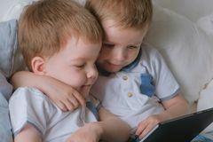 Kids with tablet. Two boys twins toddlers looking cartoon at tablet lying on the bed. Kids with tablet. Two boys twins toddlers looking cartoon at tablet lying royalty free stock photography