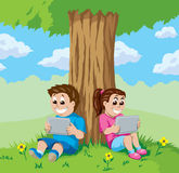 Kids with tablets under a tree Stock Image