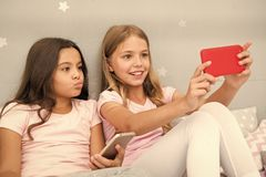 Kids taking selfie in bedroom. Pajamas party concept. Girlish leisure happy childhood. Girls long hair with smartphones stock images