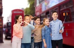 Kids taking selfie by smartphone over london city. Childhood, travel, tourism, technology and people concept - happy children talking picture by smartphone on stock images