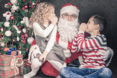 Kids talk to Santa Claus about wishlist, gifts, Christmas night Royalty Free Stock Photos