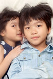 Kids talking on bed. Kids talking while lying on bed royalty free stock photography