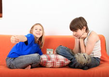 Kids talking about housing. Smiling girl and serious boy - kids talking about housing with a plastic house on pillow between them royalty free stock photography